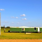 Green Mobile Home Blue Sky Raw Sienna Dirt Hwy East From